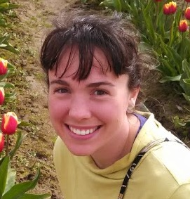 a headshot of me with bangs sitting in a field of tulips